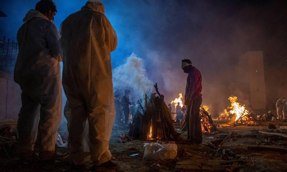 Pessoas paramentadas contra a Covid-19 cremam corpos de vítimas da pandemia em Nova Délhi, na Índia Foto: DANISH SIDDIQUI / REUTERS