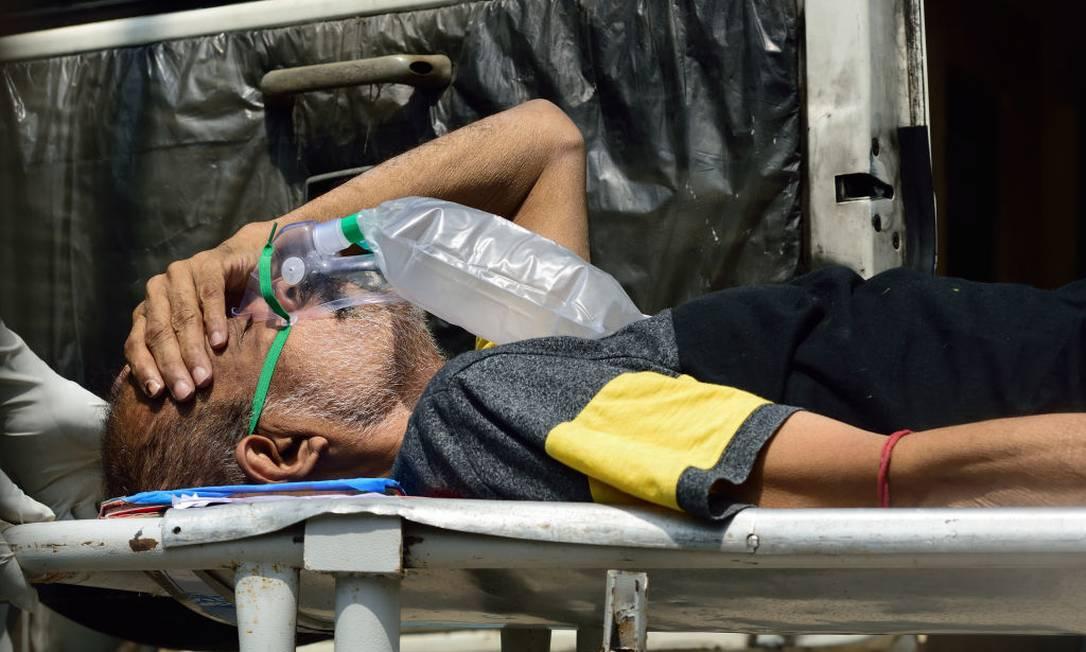 Paciente com Covid-19 usa máscara de oxigênio e aguarda internação em hospital de Calcutá Foto: Anadolu Agency / Anadolu Agency via Getty Images