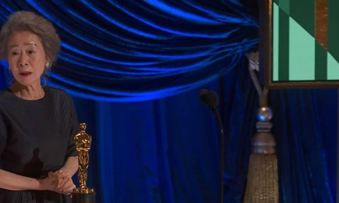 """Yoon Yeo-jeong recebe a estatueta de Melhor Atriz Coadjuvante por """"Minari"""", longa que também concorre a Melhor Filme. Yoon, em um discurso comovente e bem humorado, disse que dessa vez apenas teve """"mais sorte"""" do que as concorrentes. Foto: Reprodução"""