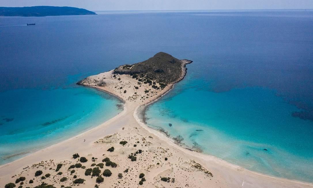 Praia em Elafinisos, uma das ilhas gregas onde a vacinação contra Covid-19 está adiantada por conta da reabertura das atividades turísticas, em maio Foto: ARIS MESSINIS / AFP