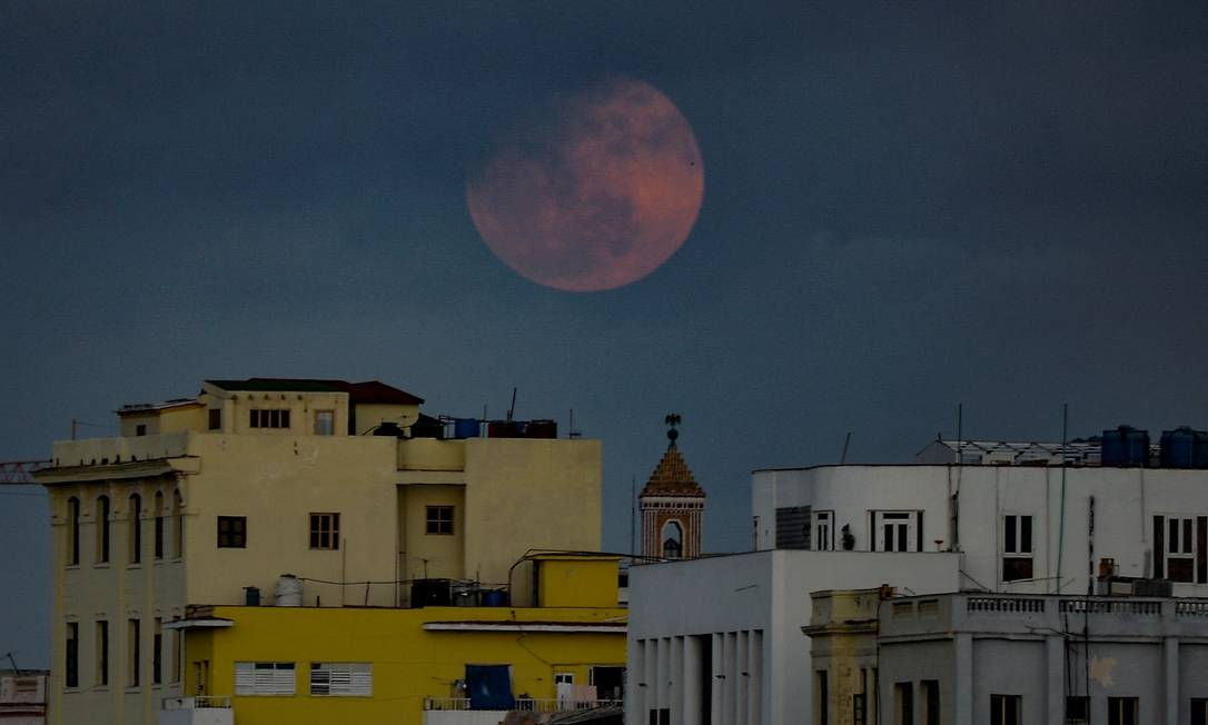 """A """"super pink moon"""" completa é vista sobre edifícios de Havana, capital de Cuba Foto: YAMIL LAGE / AFP"""