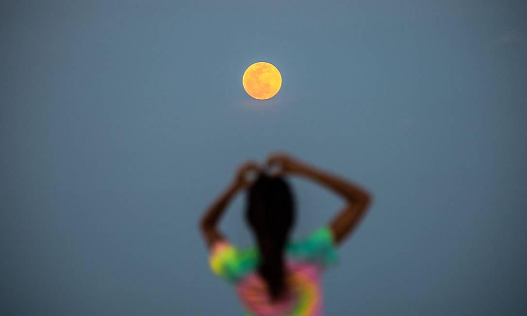 Mulher observa super pink moon na praia em Miami Beach, nos Estados Unidos Foto: CHANDAN KHANNA / AFP