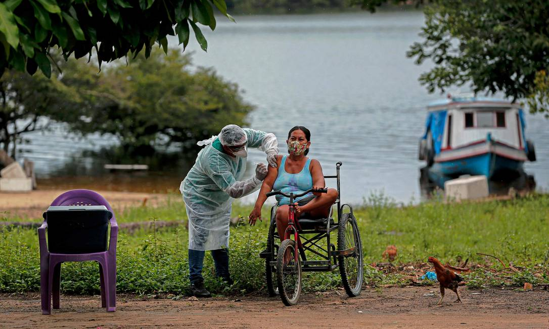 Profissional de saúde da Secretaria de Saúde Indígena do Ministério da Saúde administra uma segunda dose da vacina contra COVID-19 a uma mulher da aldeia Esperança do Rio Arapiun, no Baixo Amazonas, estado do Pará, próximo a Santarém Foto: TARSO SARRAF / AFP