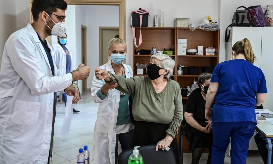 Paciente cumprimenta um membro da equipe médica no centro de saúde da ilha grega e Elafonissos, depois de receber dose da vacina contra Covid-19 Foto: ARIS MESSINIS / AFP