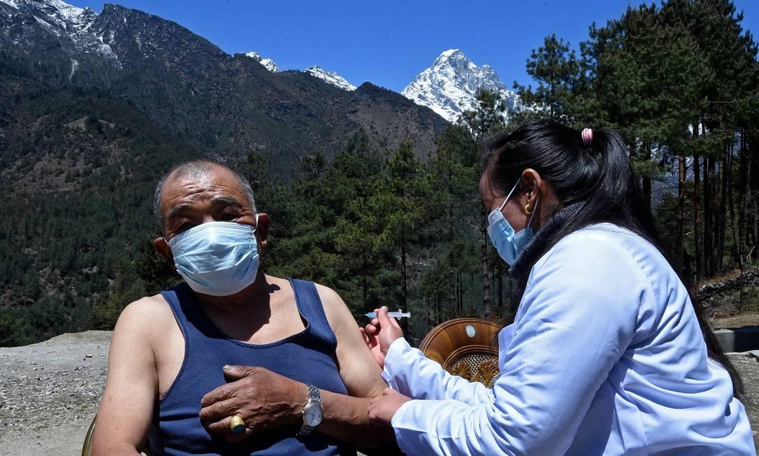 Um profissional de saúde inocula um homem com a dose da vacina Covishield contra o Covid-19 em um posto de saúde perto de Lukla, no nordeste do Nepal Foto: PRAKASH MATHEMA / AFP