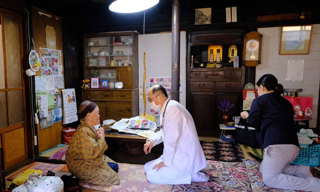 Profissionais de saúde conversam com Kakino Yamaguchi, depois de chegar a sua casa para inoculá-la com a vacina de coronavírus Pfizer-BioNTech Covid-19, na vila de Kitaaiki, onde vivem cerca de 350 famílias, na província de Nagano, no Japão Foto: KAZUHIRO NOGI / AFP