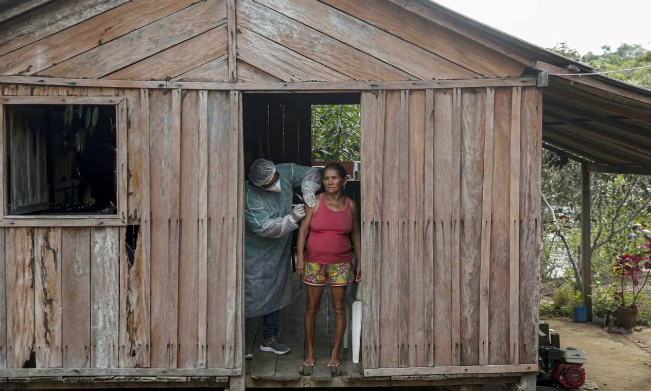 Trabalhador de saúde do Departamento de Saúde Indígena do Ministério da Saúde administra uma segunda dose de uma vacina COVID-19 à paciente Maria Tereza em São José III do rio Maro, na região do Baixo Amazonas no estado do Pará, próximo a Santarém Foto: TARSO SARRAF / AFP