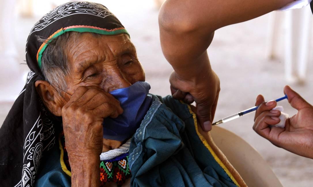 Indígena Wixarica é imunizada com a vacina CanSino Biologics contra COVID-19 no centro de vacinação instalado na cidade de Nuevo Colonia, em Mezquitic, estado de Jalisco, México Foto: ULISES RUIZ / AFP