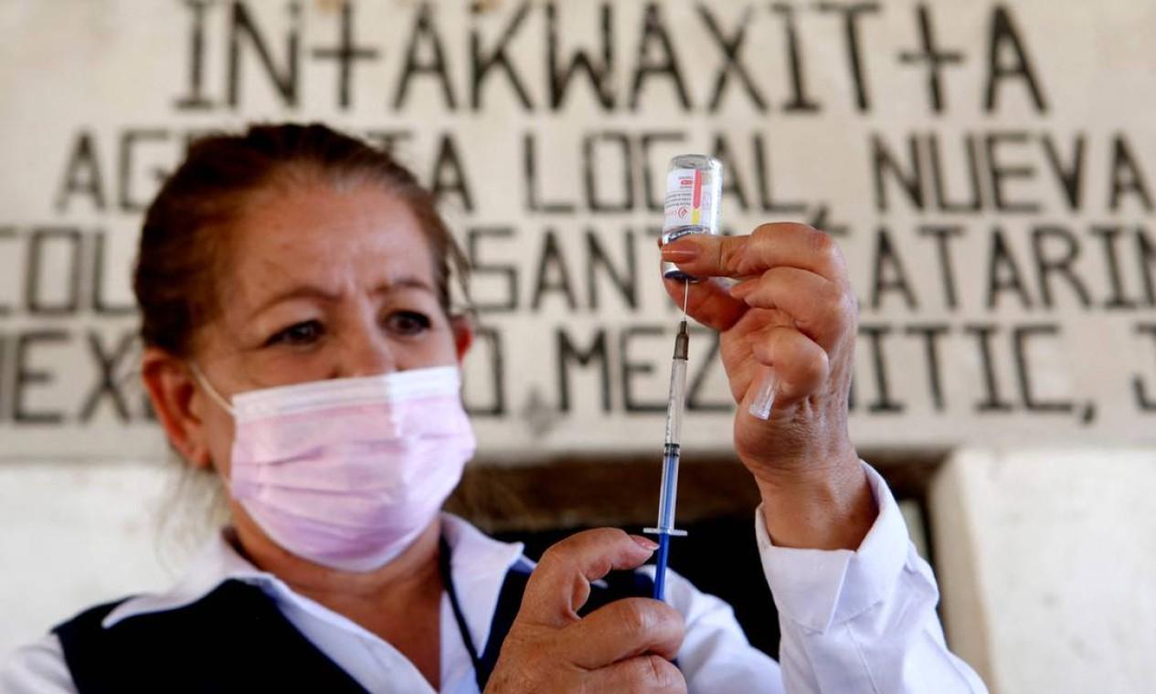 Uma enfermeira prepara uma dose da vacina COVID-19 da CanSino Biologics, no centro de vacinação instalado na cidade de Nuevo Colonia, em Mezquitic, estado de Jalisco, México Foto: ULISES RUIZ / AFP