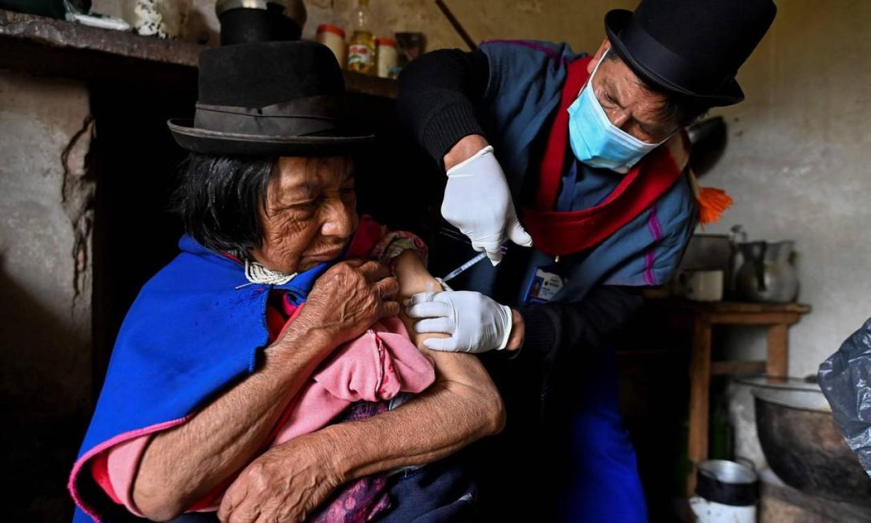 Enfermeira indígena da etnia Misak Anselmo Tunubala, 49, inocula uma idosa indígena com vacina Sinovac contra COVID-19 na reserva indígena Guambia, zona rural de Silvia, departamento de Cauca, Colômbia Foto: LUIS ROBAYO / AFP