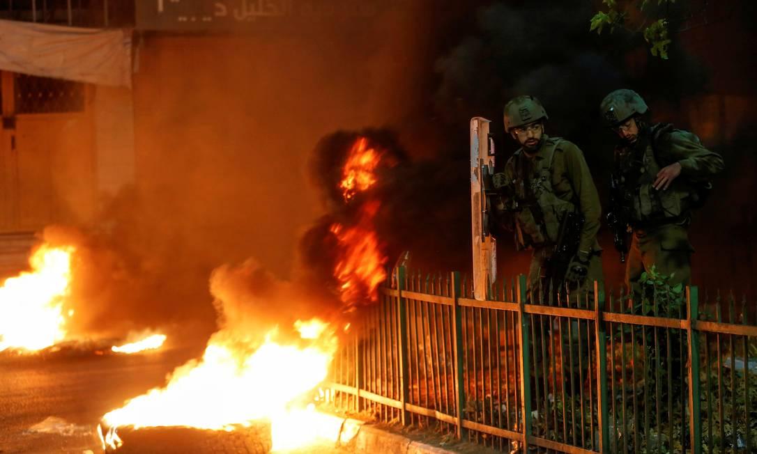 Soldados israelenses ficam ao lado de pneus em chamas enquanto palestinos participam de um protesto anti-Israel contra a tensão em Jerusalém, em Hebron, na Cisjordânia ocupada por Israel Foto: MUSSA ISSA QAWASMA / REUTERS