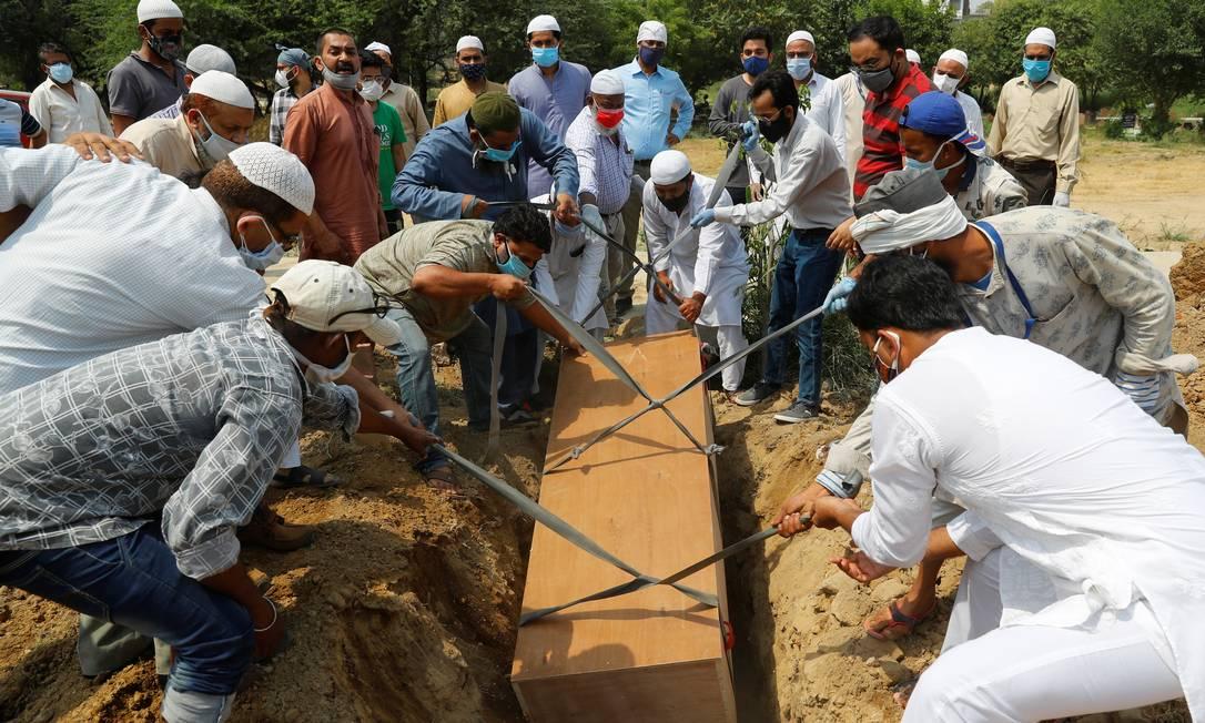 Familiares e coveiros enterram homem de 67 anos que morreu em Nova Délhi Foto: ADNAN ABIDI / REUTERS