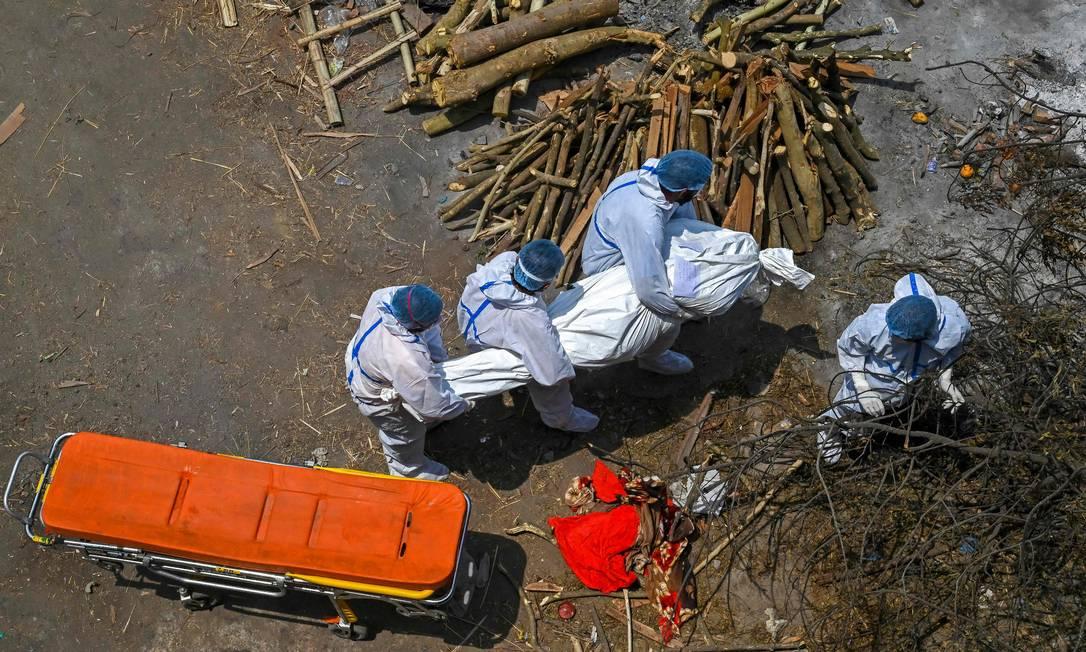 Familiares e profissionais de saúde carregam corpo de vítima da Covid-19 para cremação em Nova Délhi Foto: PRAKASH SINGH / AFP