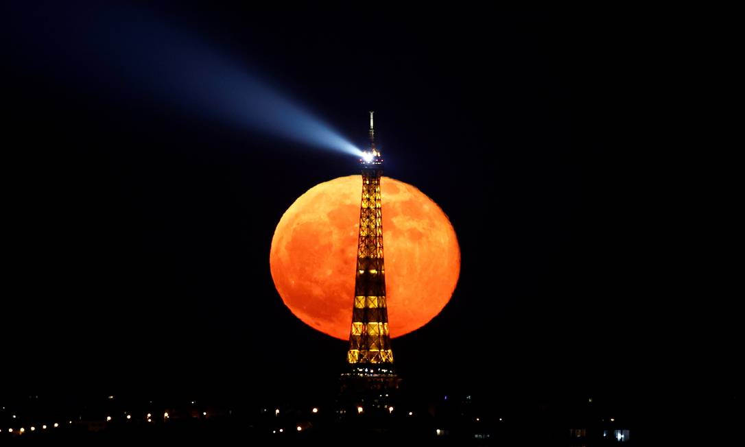 """A lua cheia, conhecida como """"Lua Super Rosa"""" surge atrás da Torre Eiffel durante um toque de recolher em todo o país devido a medidas mais rígidas contra a propagação da doença do coronavírus, em Paris, França Foto: CHRISTIAN HARTMANN / REUTERS"""