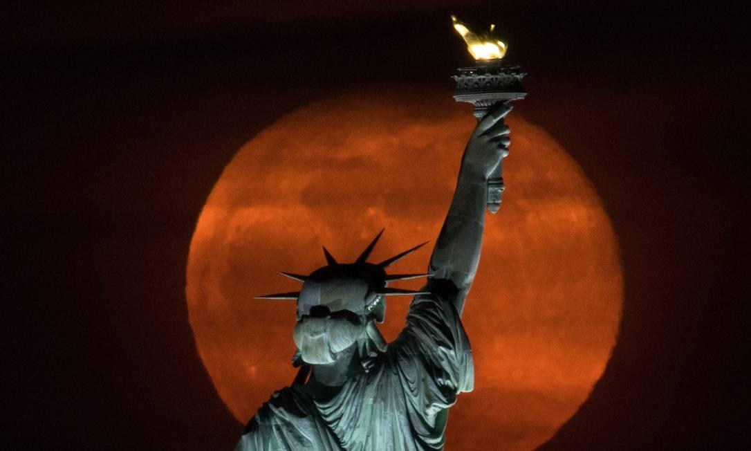 """A lua cheia, conhecida como """"Lua Super Rosa"""" surge atrás da Estátua da Liberdade na cidade de Nova York, EUA Foto: STRINGER / REUTERS"""
