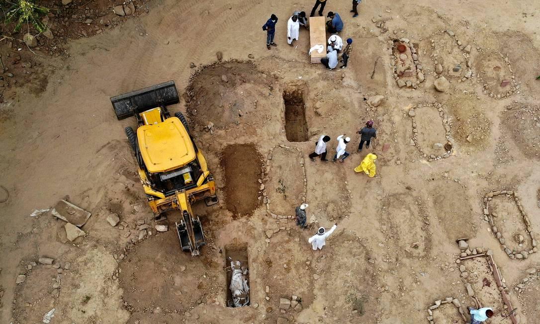 Foto aérea tirada mostra parentes e amigos reunidos para enterrar vítimas do coronavírus em um cemitério em Nova Delhi Foto: ARCHANA THIYAGARAJAN / AFP