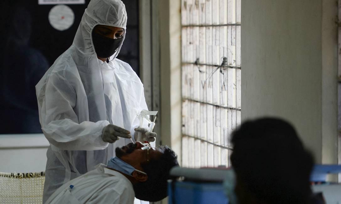 Profissional de saúde coleta uma amostra de esfregaço de um homem para realizar um teste de coronavírus RT-PCR em Chennai, em 28 de abril de 2021 Foto: ARUN SANKAR / AFP