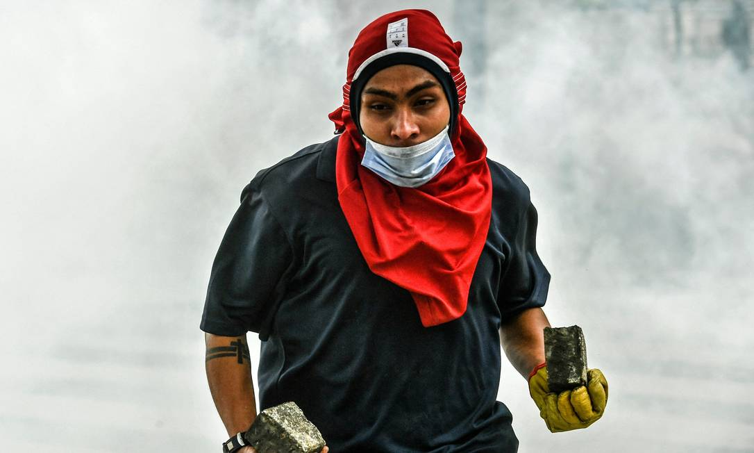 Manifestante se prepara para atirar pedras na tropa de choque durante confrontos após um protesto contra o projeto de reforma tributária lançado pelo presidente colombiano Ivan Duque, em Medellín Foto: Joaquin Sarmiento / AFP