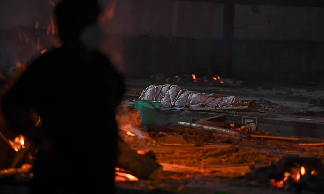 Cadáver de uma vítima do coronavírus Covid-19 antes da cremação ao lado de piras de outras vítimas no Crematório Nigambodh Ghat em Nova Delhi, Índia Foto: TAUSEEF MUSTAFA / AFP