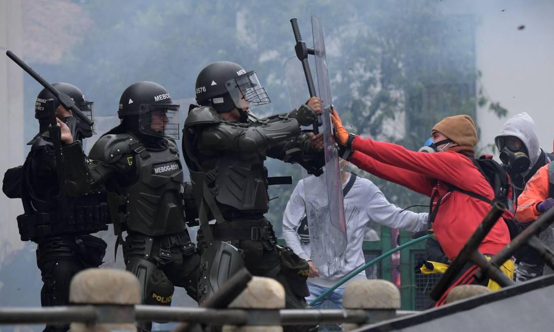 Manifestantes enfrentam a polícia durante manifestação contra a reforma tributária proposta pelo presidente colombiano Ivan Duque, em Bogotá Foto: Raul Arboleda / AFP