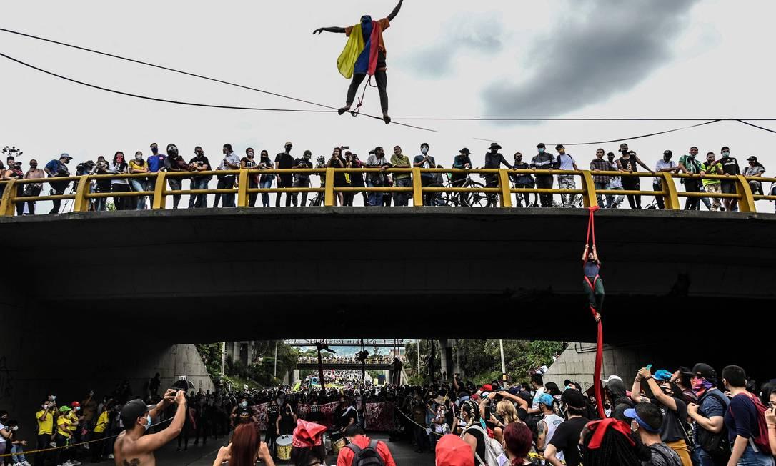 Manifestantes fazem acrobacias durante protesto contra projeto de reforma tributária lançado pelo presidente colombiano Iván Duque, em Medellín Foto: Joaquin Sarmiento / AFP