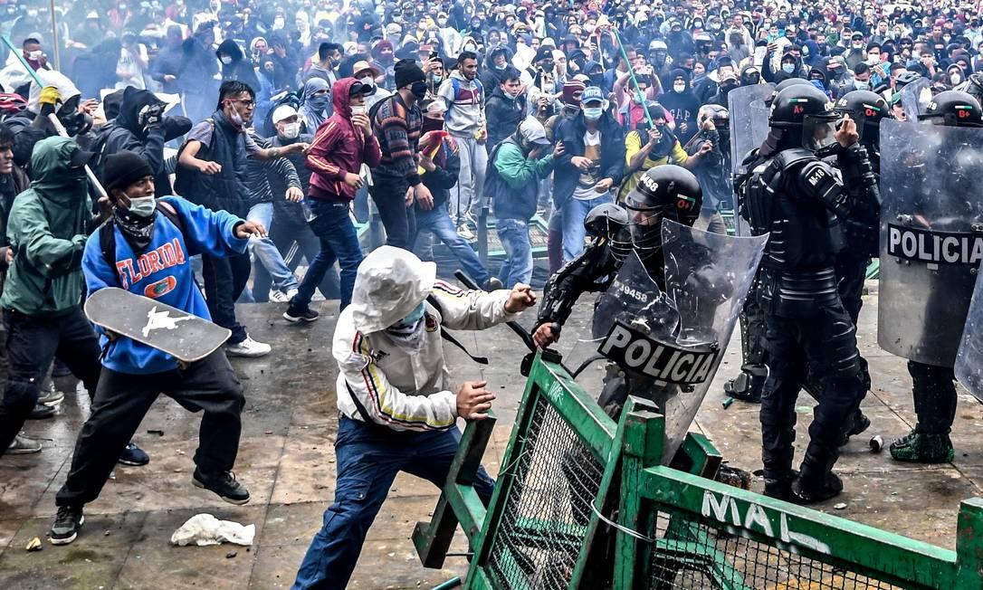 Manifestantes enfrentam tropas de choque durante protesto contra projeto de reforma tributária lançado pelo presidente colombiano Ivan Duque, em Bogotá Foto: Juan Barreto / AFP