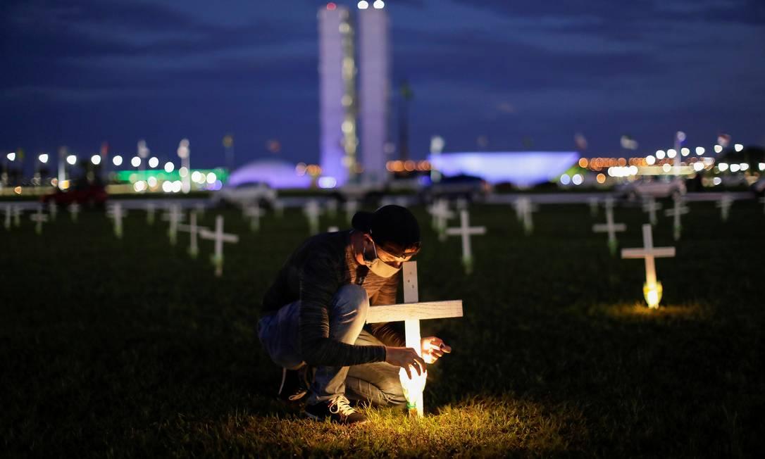 Homem acende uma vela ao lado de uma cruz simbolizando os que morreram por Covid-19, em frente ao Congresso Nacional, em Brasília Foto: Ueslei Marcelino - 27/04/2021 / Reuters