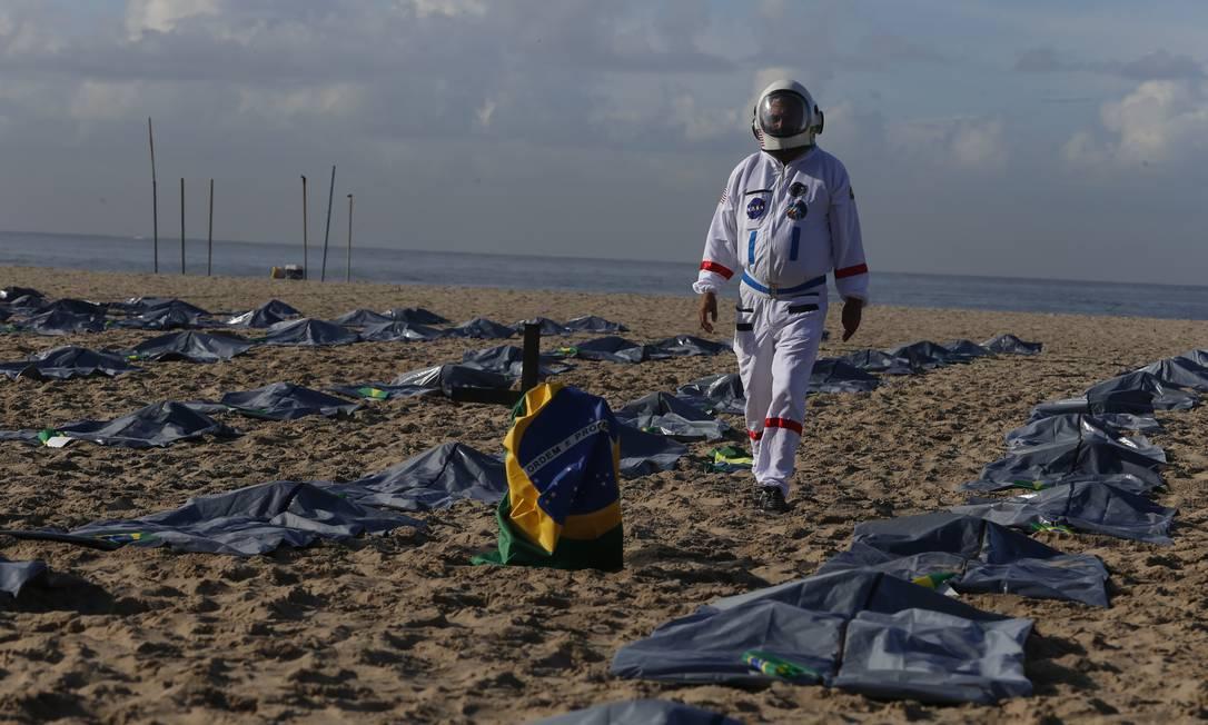 Manifestante caminha entre sacos usados na remoção de corpos para simbolizar as vítimas da pandemia Foto: Fabiano Rocha / Agência O Globo