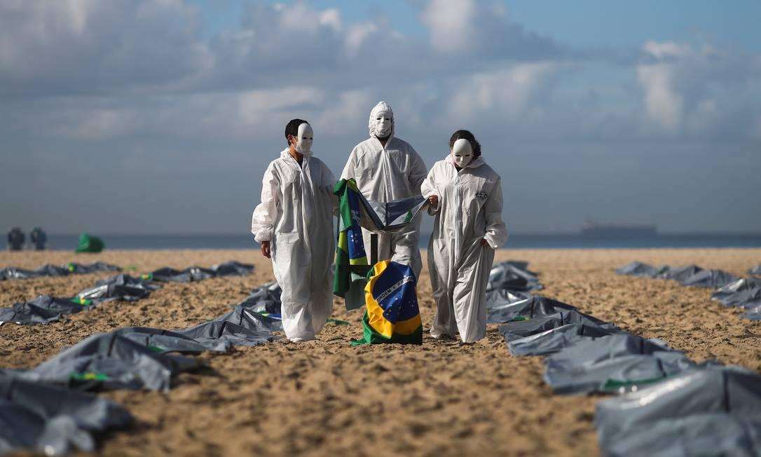 Ativistas da ONG Rio de Paz carregam bandeira brasileira enquanto exibem centenas de sacolas plásticas, representando cadáveres, durante protesto contra a política COVID-19 de Jair Bolsonaro, em meio ao surto da doença coronavírus (COVID-19), na praia de Copacabana, Zona Sul do Rio de Janeiro Foto: Pilar Olivares / REUTERS