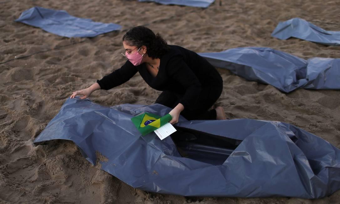 Mulher ajusta uma das sacolas plásticas representando cadáveres, expostas por ativistas da ONG Rio de Paz durante protesto contra a gestão da pandemia de Jair Bolsonaro Foto: Pilar Olivares / Reuters
