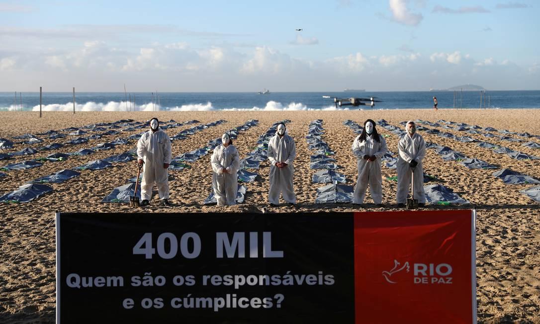 """Uma faixa com os dizeres """"400 mil, quem são os responsáveis e cúmplices?"""" é vista na frente de ativistas da ONG Rio de Paz usando máscaras e EPI enquanto exibem centenas de sacolas plásticas Foto: Pilar Olivares / Reuters"""
