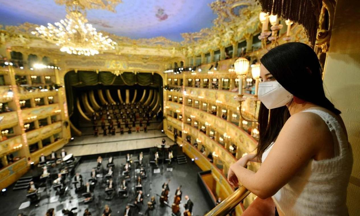 De máscara, uma espectadora acompanha um concerto na Ópera La Fenice, em Veneza, reaberta em 26 de abril, quando a Itália autorizou a volta de atividades parcias em espaços como teatros, museus, bares e restaurantes Foto: ANDREA PATTARO / AFP