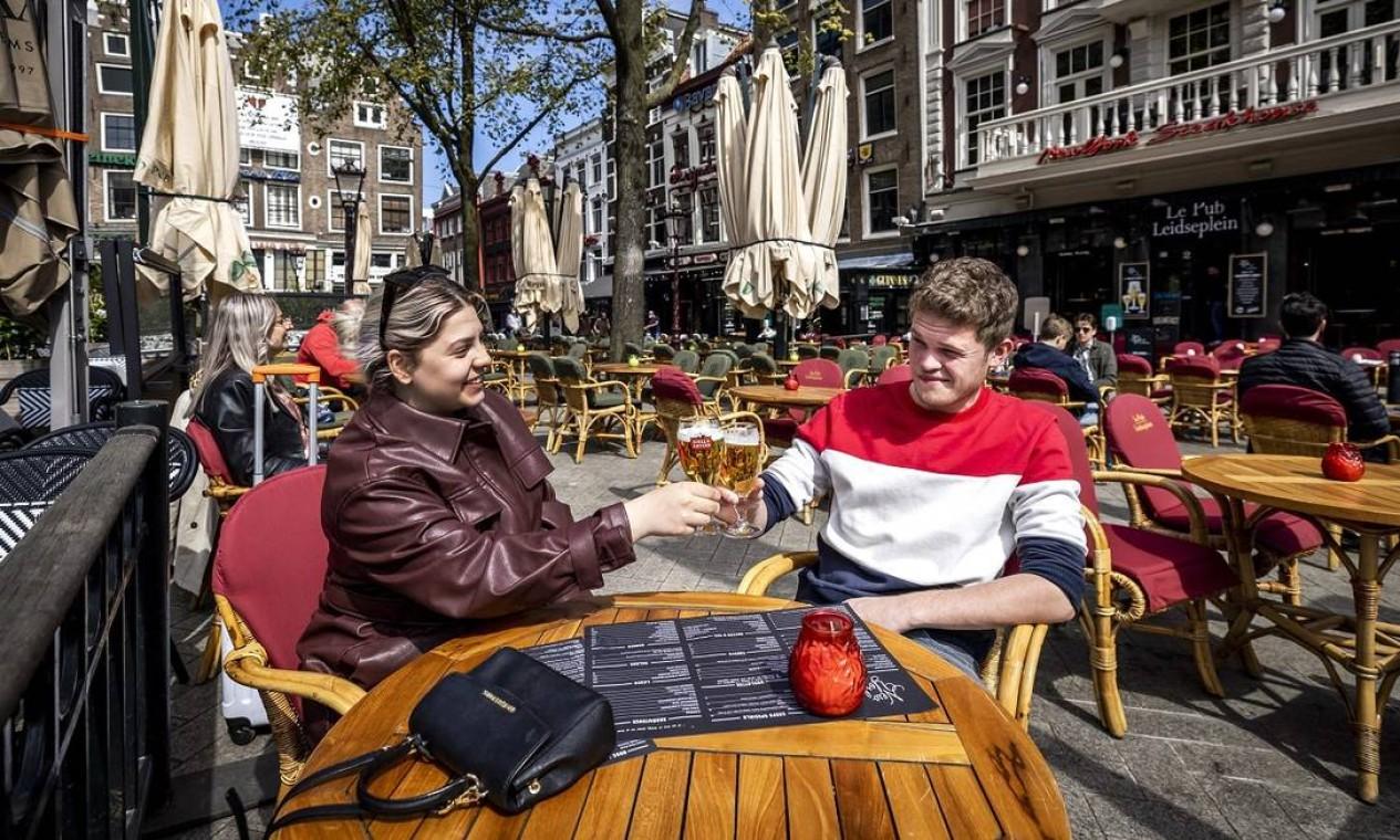 Na Holanda, a decisão do governo nacional de reabrir bares e cafés para serviços ao ar livre, desde o dia 28 de abril, foi celebrada com brindes nas ruas de Amsterdã Foto: REMKO DE WAAL / AFP