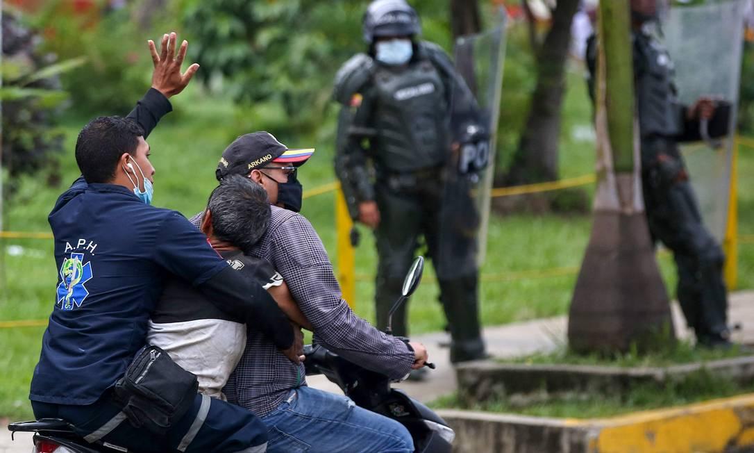 Um manifestante ferido é levado em uma motocicleta por outros homens durante confrontos com a polícia em protesto em Cali, Colômbia Foto: PAOLA MAFLA / AFP