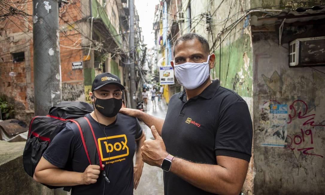 Na Rocinha, no Rio, delivery de comida beneficia trabalhadores como Rômulo Leite e empresas como a de Alexandre Araújo (à direita) Foto: Ana Branco