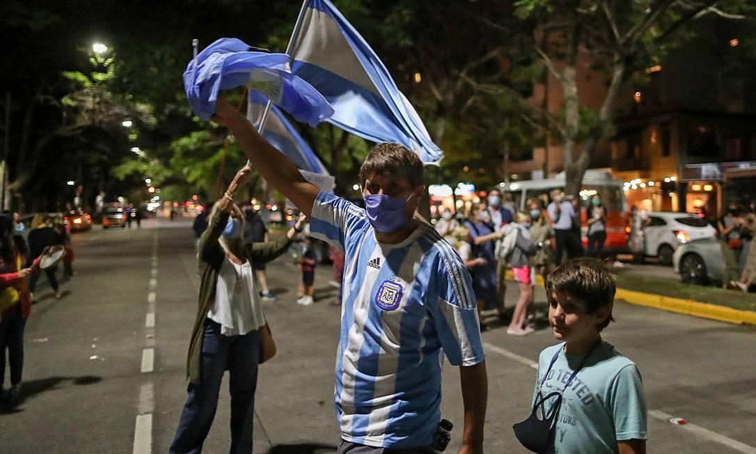 Pai com filho em manifestação contra fechamento de escolas perto da residência presidencial de Olivos; resistência à restrições é maior do que na primeira onda Foto: AGUSTIN MARCARIAN / REUTERS/14-4-2021