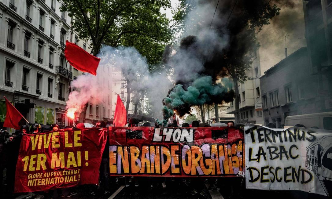 Os manifestantes queimam sinalizadores e seguram faixas com os dizeres 'Viva 1º de maio' e 'Organizados juntos' durante o comício anual do Dia do Trabalho (Dia do Trabalho) na cidade de Lyon, no sudeste da França Foto: JEFF PACHOUD / AFP