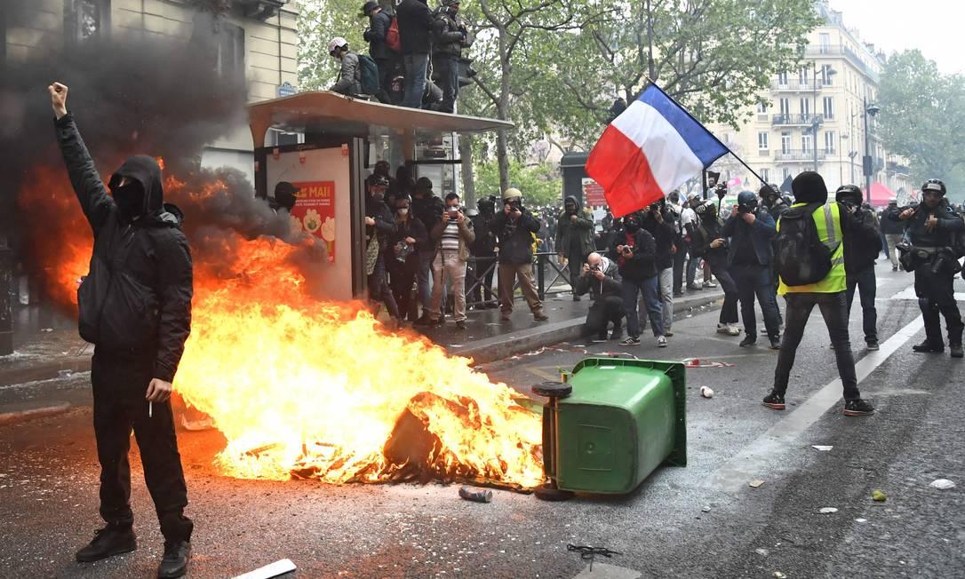 Manifestantes estão perto de uma lata de lixo em chamas na rua durante o comício anual do Dia do Trabalho em Paris, França Foto: BERTRAND GUAY / AFP