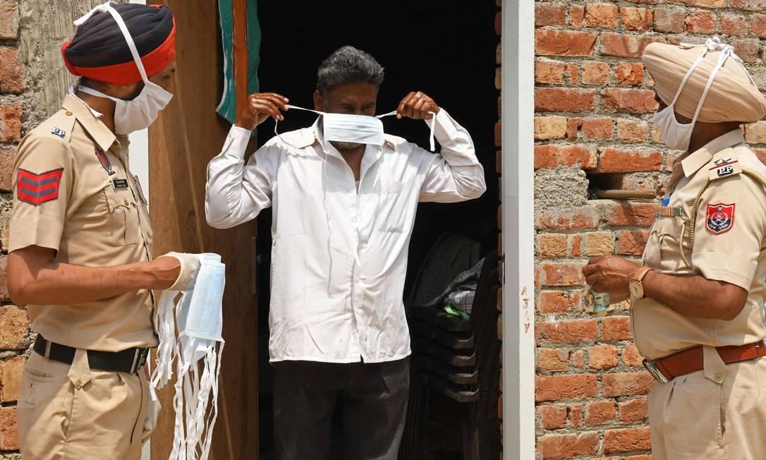 Policiais distribuem máscara facial para população em áreas rurais durante campanha de combate ao coronavírus nos arredores de Amritsar Foto: NARINDER NANU / AFP