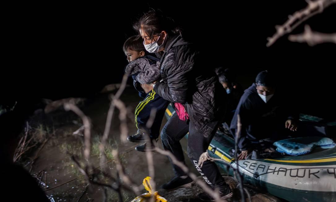 Mãe carrega seu filho durante travessia da fronteira do México com os EUA Foto: JOHN MOORE / AFP