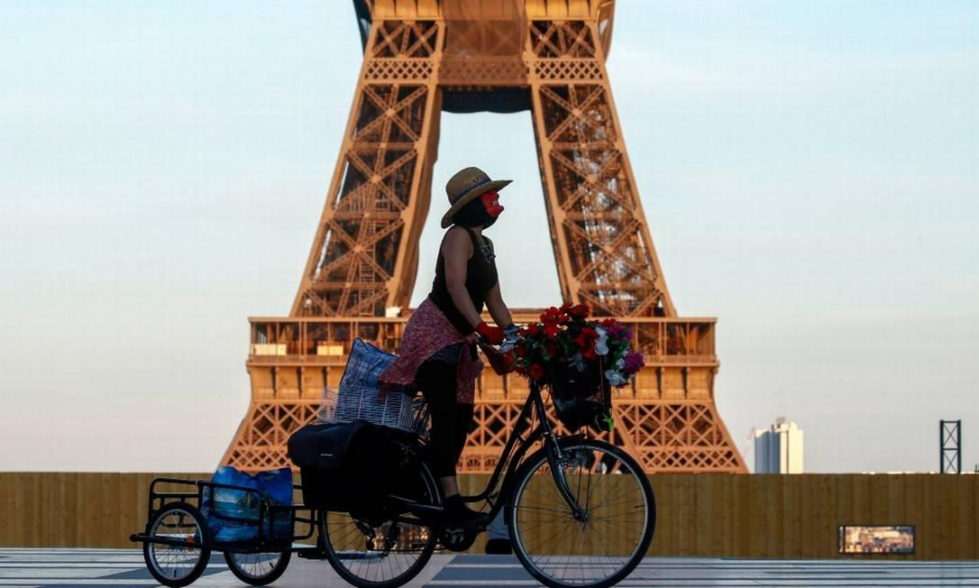 De máscara, mulher pedala em frente à Torre Eiffel, em Paris Foto: GONZALO FUENTES / REUTERS/26-4-21