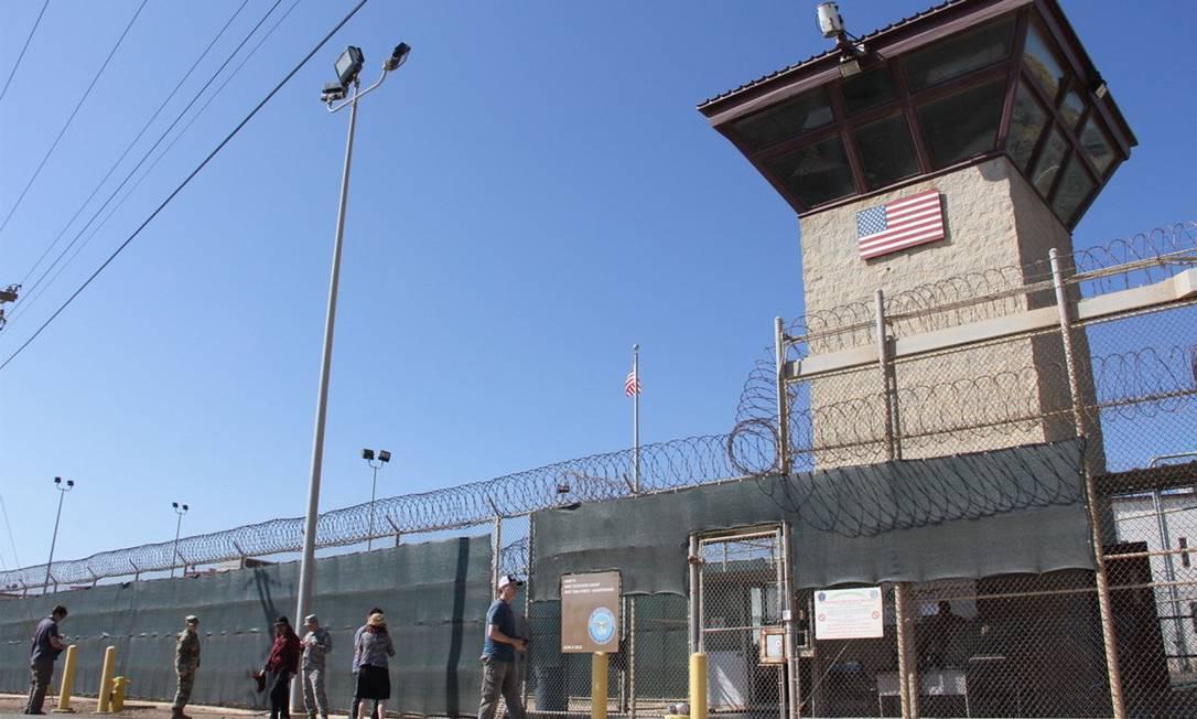 Pessoas caminham em frente a uma das torres da prisão americana de Guantánamo, em Cuba Foto: THOMAS WATKINS / AFP