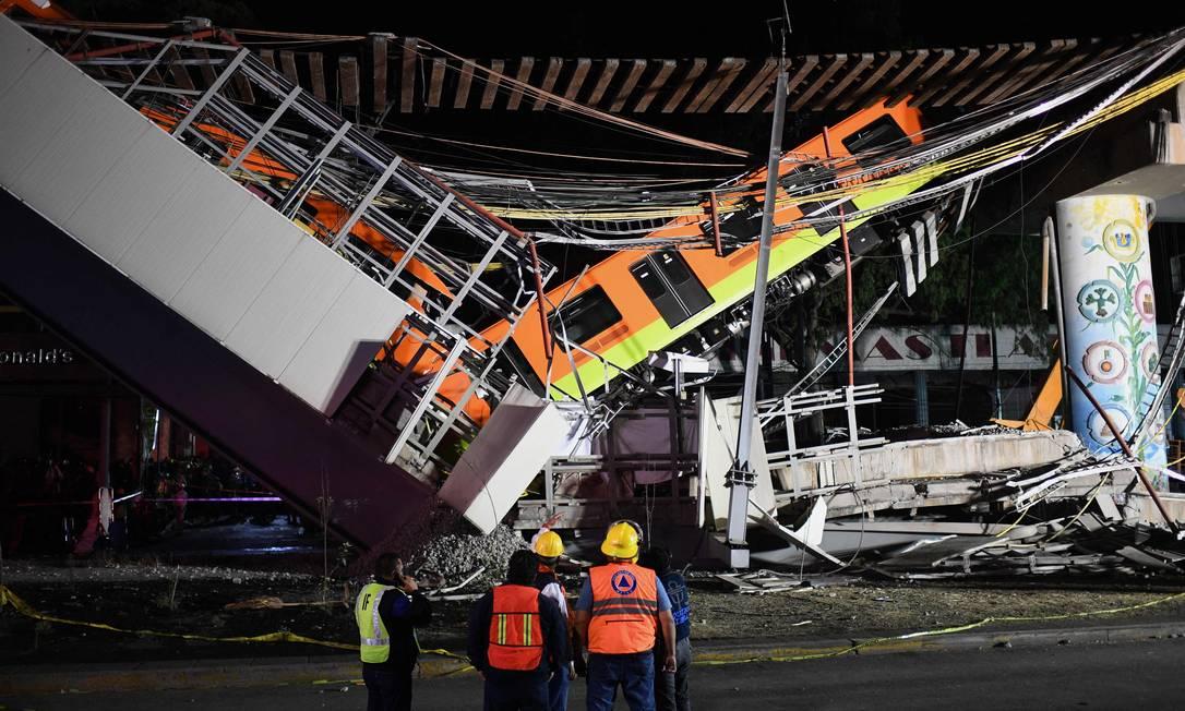 Equipes de resgate trabalham nos vagões do metrô que ficaram pendurados sobre o viaduto que desabou na Cidade do México Foto: PEDRO PARDO / AFP