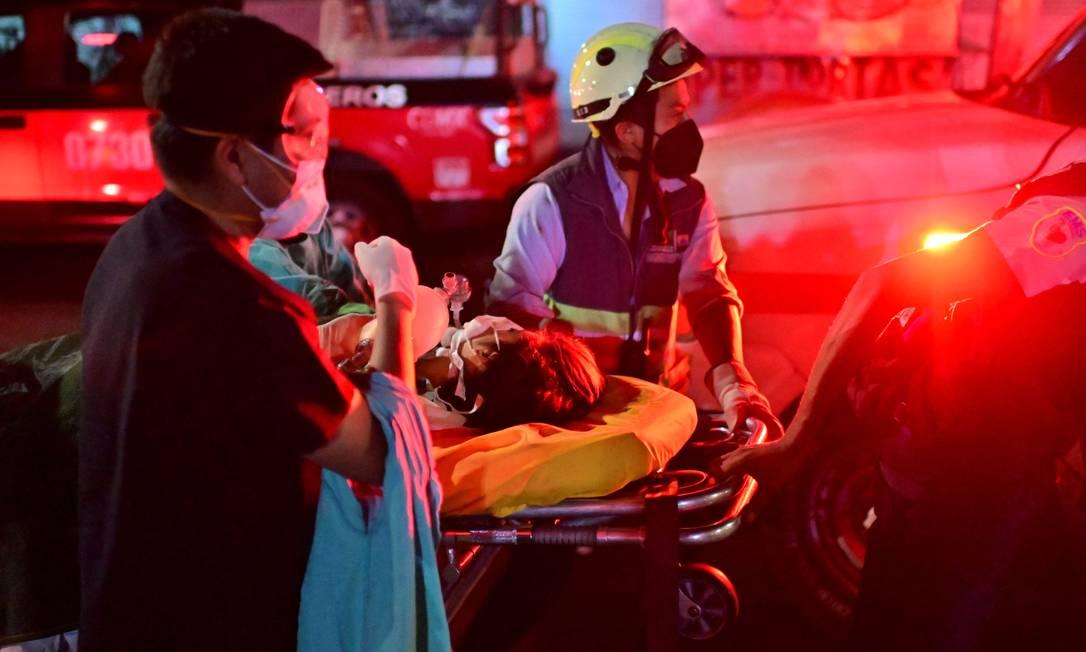 Trabalhadores de emergência movem uma pessoa ferida em uma maca no local do acidente Foto: PEDRO PARDO / AFP