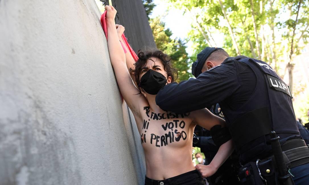 Policial espanhol detém ativista do Femen protestando contra o partido de extrema direita Vox da Espanha, em frente a uma seção eleitoral em Madri, durante as eleições regional. A capital espanhola está votando em uma eleição regional antecipada do atual Partido Popular conservador, favorito a vencer confortavelmente, a contragosto do primeiro-ministro socialista da Espanha, Pedro Sánchez Foto: PIERRE-PHILIPPE MARCOU / AFP