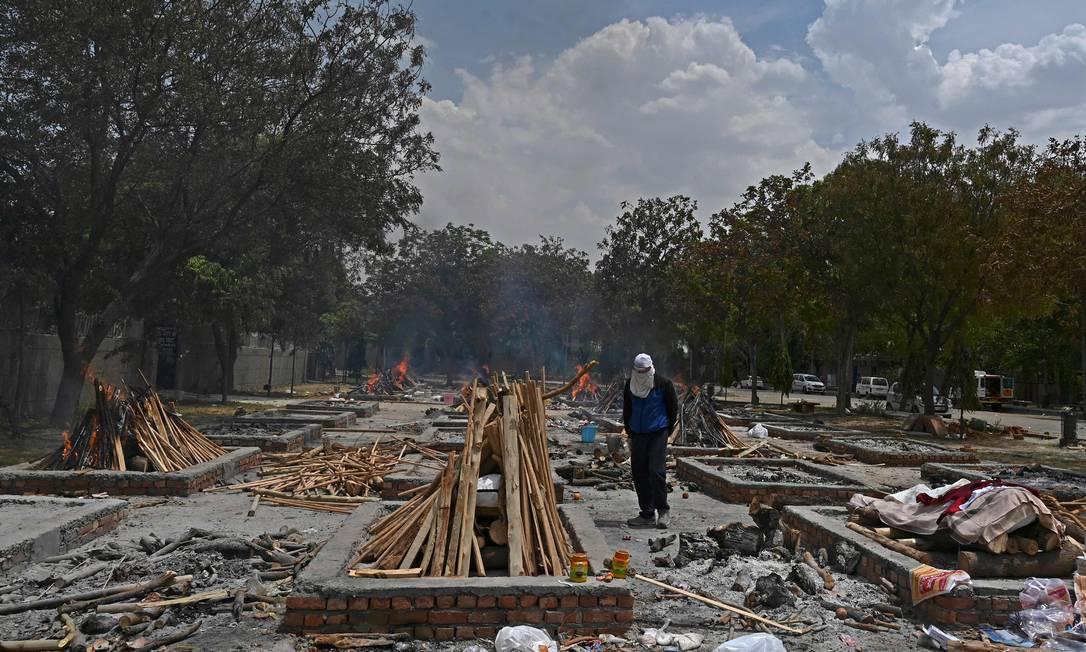 Homem está ao lado de fogueiras preparadas para cremar vítimas que morreram do coronavírus Covid-19, em Nova Delhi. A Índia ultrapassou a marca de 20 milhões de casos confirmados da doença Foto: TAUSEEF MUSTAFA / AFP