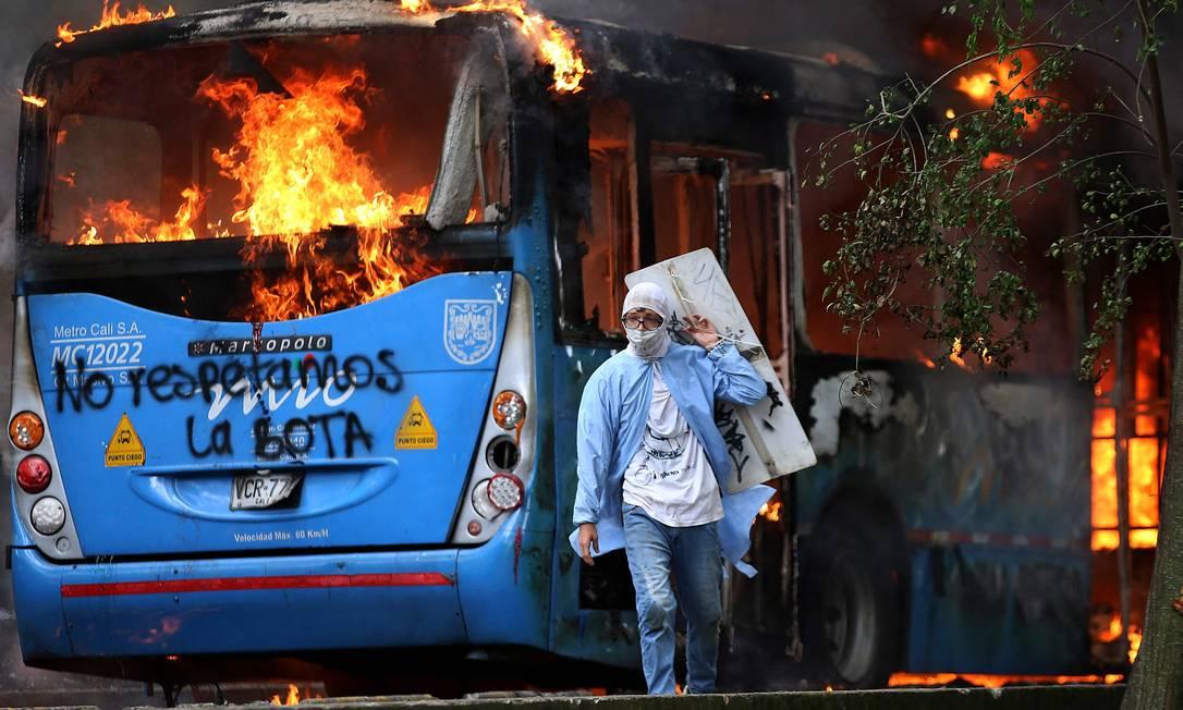Homem caminha em frente a um ônibus de transporte público em chamas durante um protesto contra um projeto de reforma tributária lançado pelo presidente colombiano Iván Duque, em Cali Foto: PAOLA MAFLA / AFP