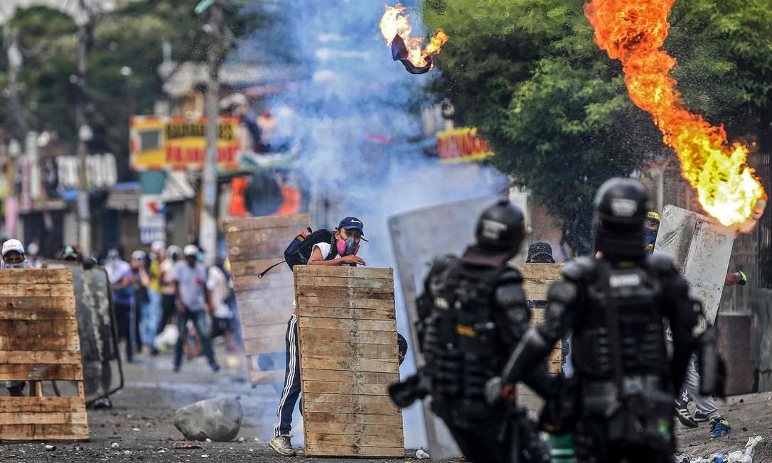 Manifestantes enfrentam tropas de choque durante protesto contra projeto de reforma tributária lançado pelo presidente colombiano Ivan Duque, em Cali Foto: PAOLA MAFLA / AFP