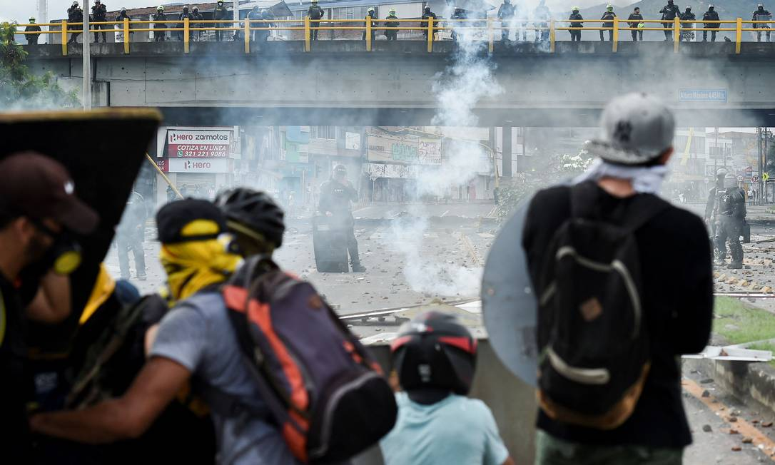 Manifestantes enfrentam tropas de choque durante confrontos em Cali Foto: LUIS ROBAYO / AFP
