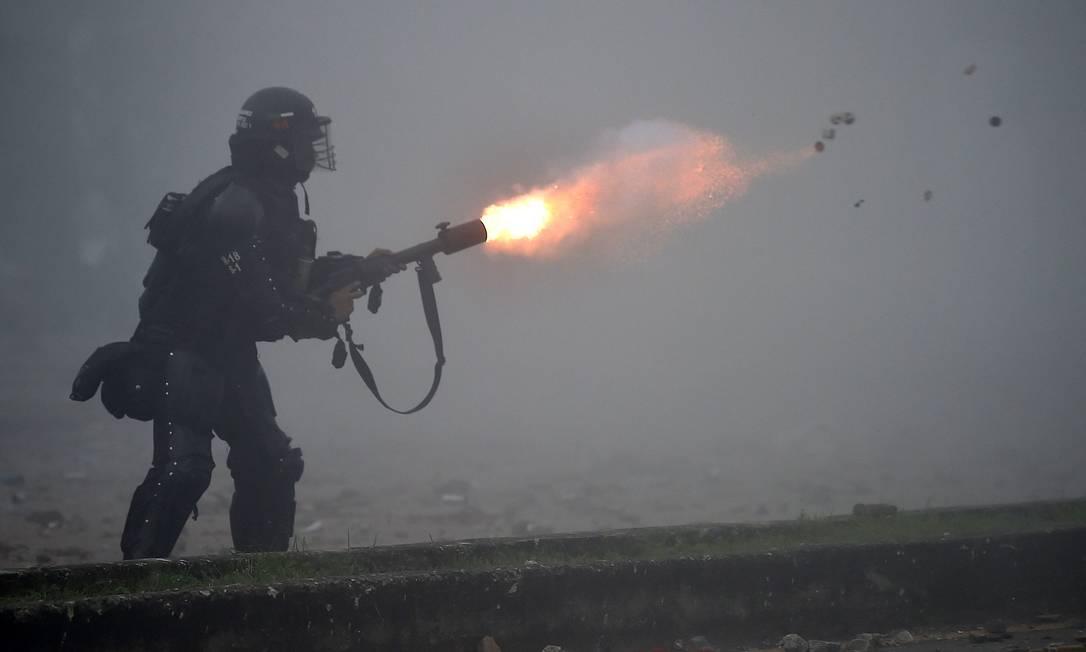 Policial de choque dispara gás lacrimogêneo contra manifestantes Foto: LUIS ROBAYO / AFP